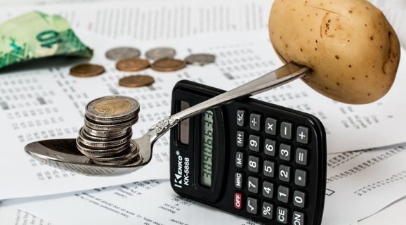 balancing coins and potato on a spoon balanced on a calculator